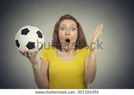 Surprise astonished woman. Closeup portrait woman with soccer ball looking surprised in full disbelief wide open mouth isolated grey wall background. Human emotion facial expression body. Funny girl - stock photo