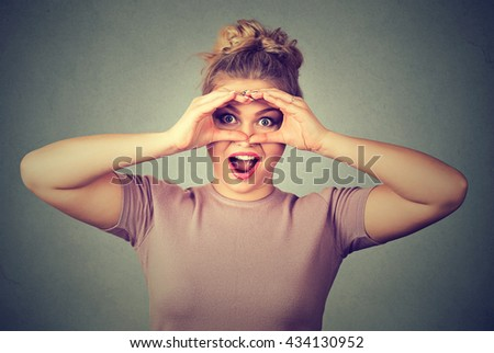 Surprise. Closeup portrait young stunned curious woman peeking looking through fingers like binoculars searching something isolated on gray wall background. Face expression reaction - stock photo