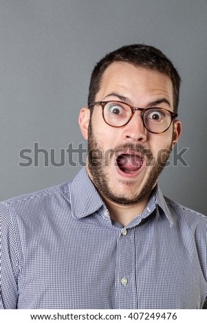 surprise concept - happy young bearded corporate man with eyeglasses and mouth open to express amazement or having a great idea, grey background studio