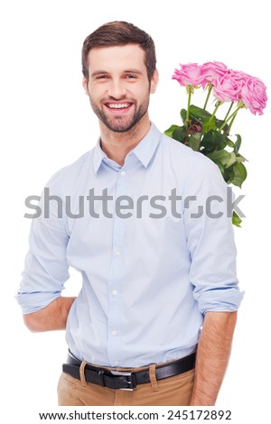 Surprise for her. Handsome young man hiding a bouquet with pink roses behind back and smiling while standing isolated on white background   - stock photo