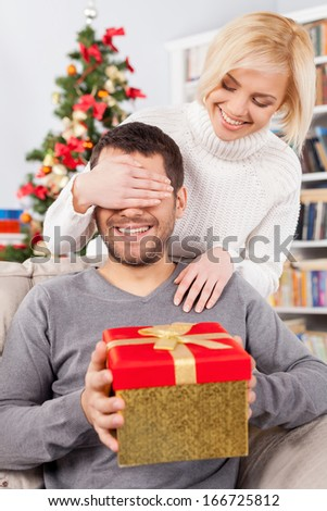 Surprise! Handsome young man sitting on the couch and holding a gift box while her girlfriend standing behind him and covering his eyes with hands - stock photo
