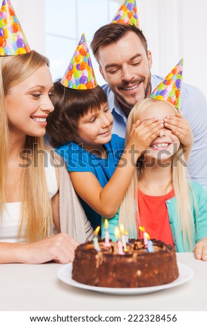 Surprise! Happy family of four celebrating birthday of happy little girl sitting at the table while her brother covering her eyes with hands and smiling - stock photo