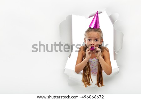Surprise - little girl with party horn popping out from a torn paper sheet - with copy space