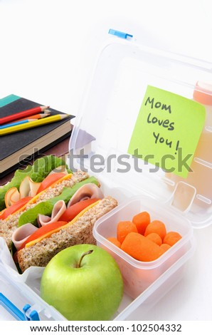 Surprise postie message in school lunch box filled with sandwiches and healthy food - stock photo