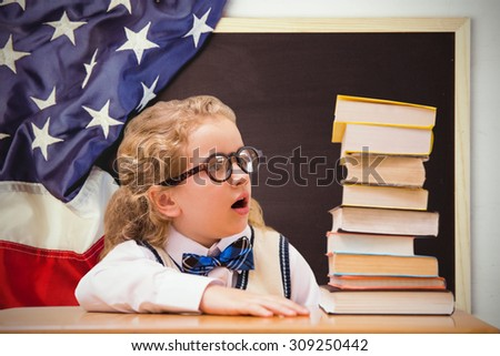 Surprise pupil looking at books against american flag on chalkboard - stock photo