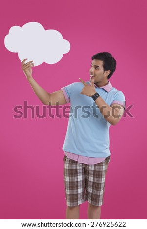 Surprise young man pointing at thought bubble over pink background - stock photo