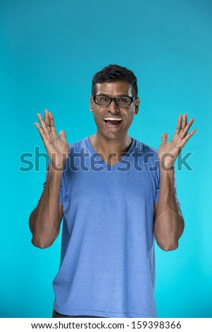Surprised and amazed looking Indian man standing against blue background. - stock photo