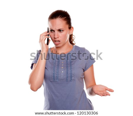 Surprised and angry woman speaking on cellphone on blue shirt standing over white background - stock photo
