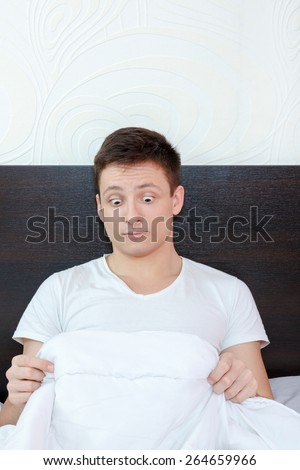 surprised and shocked good looking young man in bed looking down at his penis under white covers sheet in bedroom. Concept photo of male sexuality and man sex peny problems, domestic atmosphere. - stock photo