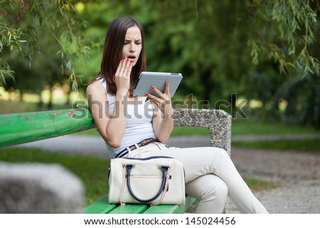 Surprised and worried young woman getting bad news on tablet computer / huge smartphone - stock photo
