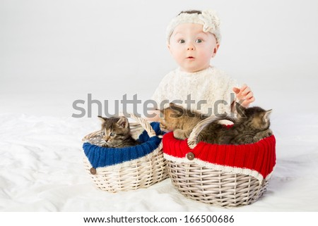 Surprised baby girl dressed in white fur with two basket with small kittens