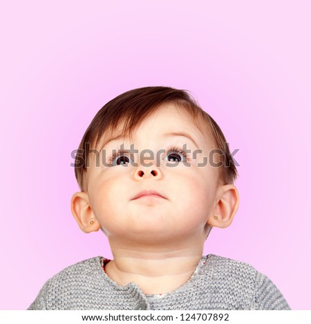 Surprised baby girl looking up isolated on pink background - stock photo