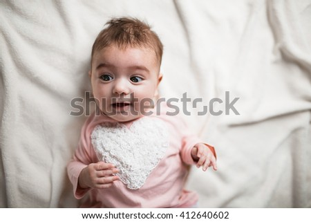 surprised baby in bed - stock photo