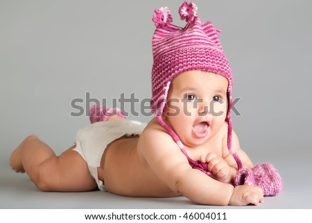 Surprised baby in pink cap laying on gray background - stock photo
