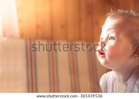Surprised baby in room with copy space - stock photo