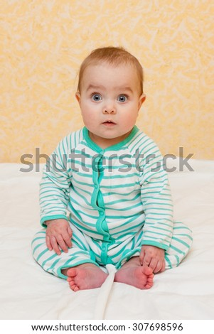 Surprised baby in striped sleep and play suit sitting on the bed. Baby looking straight at the camera. - stock photo