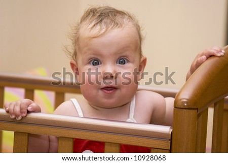 Surprised baby in the baby bed