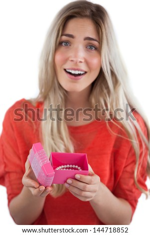 Surprised blonde woman opening gift on a white background