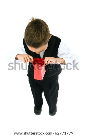 surprised boy holding red bag with a gift in his hands isolated on white