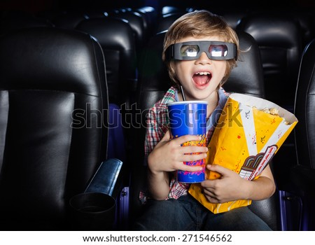 Surprised boy holding snacks while watching 3D movie in cinema theater - stock photo