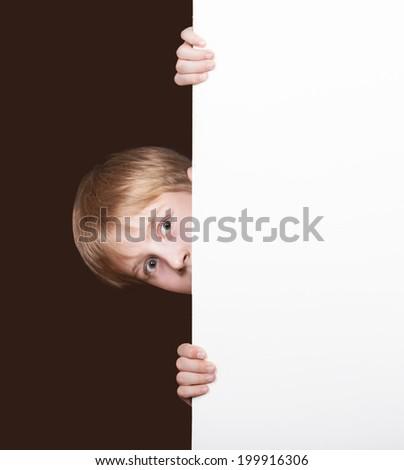 Surprised boy looking around the corner - stock photo