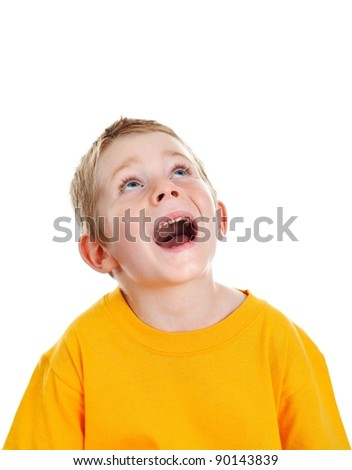 Surprised boy with open mouth looking up to white copy space