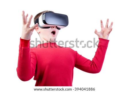 Surprised boy with virtual reality glasses wearing a red shirt against a white background holds his hands apart - stock photo