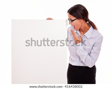 Surprised brunette businesswoman with glasses looking at a placard with her open mouth, wearing her straight hair tied back and a button down shirt, gesturing with her left hand at her mouth - stock photo
