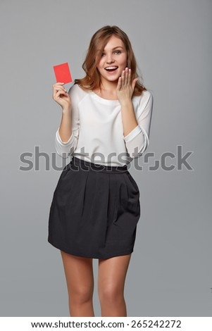 Surprised business woman showing blank credit card, over gray background. Excited businesswoman with opened mouth