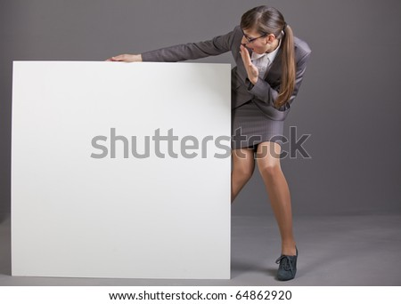 surprised business woman with blank board over grey background