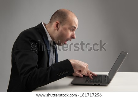 surprised businessman looking at his laptop - stock photo