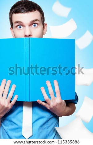 Surprised Businessman Peeping Over The Top Of A Business Planning Text Book In A Depiction Of A Market Research Idea - stock photo