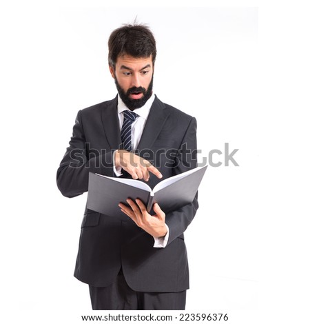 Surprised businessman reading a book over white background - stock photo