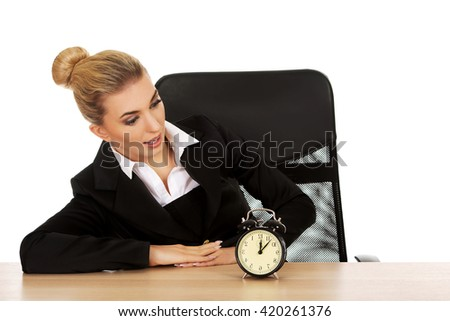 Surprised businesswoman looking at alarm clock behind the desk - stock photo