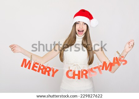 Surprised Caucasian teenage woman with Santa hat holding Merry Christmas decoration. Beautiful teen girl with long brown hair and knitted Santa Claus hat holding handcrafted holiday decoration. - stock photo