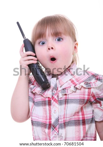 surprised child talking on the phone. little girl on the telephone - stock photo