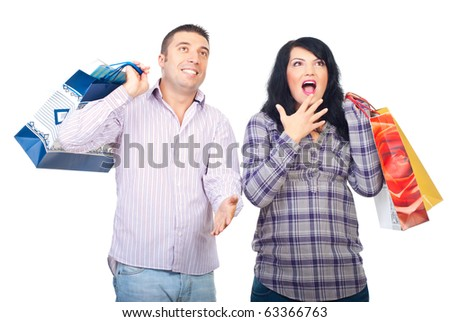Surprised couple holding shopping bags and looking up somewhere isolated on white background - stock photo