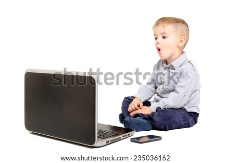 Surprised cute child sitting looking at laptop screen - stock photo
