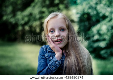 Surprised cute little blond girl at summer field. - stock photo