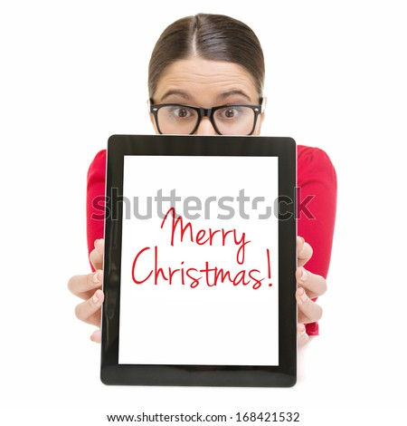 Surprised cute young Caucasian businesswoman with glasses showing digital tablet screen that states Merry Christmas. Christmas concept. - stock photo