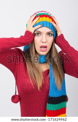 Surprised cute young Caucasian woman wearing colorful winter clothes and accessories. Stress, depression, winter fashion concept.
