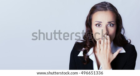 Surprised excited businesswoman covering with hands her mouth, over grey background, with blank copyspace area for advertising slogan or text message. Brunette woman in business concept studio shoot.