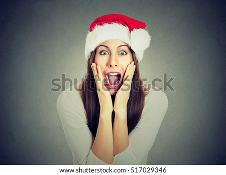 Surprised excited happy woman wearing red santa claus hat looking shocked by what she saw isolated gray background. Positive emotion