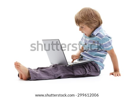 Surprised expression on a boys face whilst getting into mischief on a laptop computer concept for child internet safety, social media or education and homework - stock photo