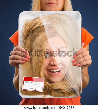 Surprised female head wrapped in food tray - stock photo