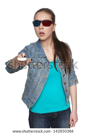 Surprised female in 3D glasses pointing with TV remote to the side, against white background - stock photo