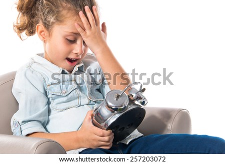 Surprised girl holding a clock
