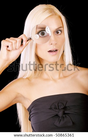 Surprised girl looks in a magnifier, isolated on black background.