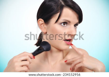 Surprised Girl with makeup brush, close up - stock photo