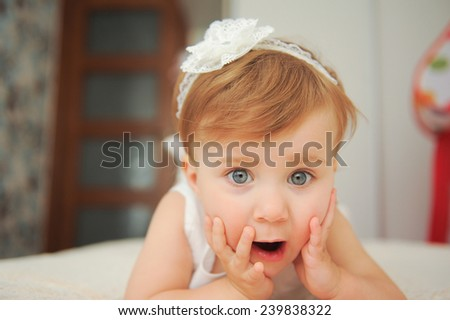 surprised girl with opened mouth lying in bed - stock photo